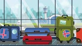 atlıkarınca : Suitcases with Iceland flag stickers on baggage carousel in airport, close-up. Icelandic tourism related loopable cartoon animation
