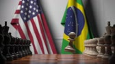 rivalidade : Chess game against flags of USA and Brazil. Political competition related 3D animation