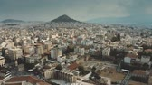 chovendo : Aerial view of the cityscape of Athens, Greece. Flight from the Acropolis towards the Lycabettus Hill Stock Footage