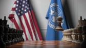 un : Flags of USA and United Nations behind pawns on the chessboard. Conceptual editorial 3D animation Stock Footage