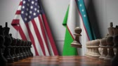 rivalidade : Flags of USA and Uzbekistan behind pawns on the chessboard. Chess game or political rivalry related 3D animation