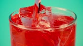kubus : Pouring red soft drink into a glass full of ice cubes against cyan background, close-up slow motion shot on Red
