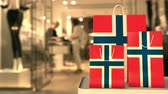 retailers : Shopping bags with flag of Norway against blurred store. Norwegian shopping related clip