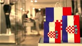 assistente : Flag of Croatia on the paper shopping bags against blurred store entrance. Retail related clip