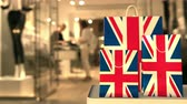 retailers : Flag of the United Kingdom UK on the paper shopping bags against blurred store entrance. Retail related clip