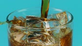 kubus : Pouring cola soft drink into a glass with ice cubes on cyan background, slow motion shot on Red