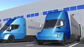 portugalia : Modern semi-trailer trucks with MADE IN PORTUGAL text being loaded or unloaded at warehouse. Portuguese business related loopable 3D animation