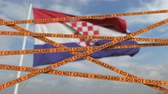 fogalmi : Biohazard restriction tape lines against the Croatian flag. Restricted entry or quarantine in Croatia. Conceptual looping 3D animation
