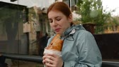 produtos de panificação : Happy redhead girl enjoy eating baguette at the bus stop