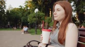 кофе : Redhead girl drinks coffee in the park