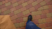 In sneakers, paving stones top view sanny day
