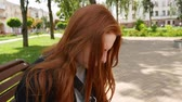 fotografo : Red-haired girl is working with a camera. Sunny day