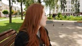 Red-haired girl in the park Stock mozgókép