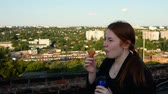 çatılar : Red-haired girl drinks coffee and eats croissants on the roof of the house. Stok Video