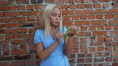 Girl in a blue dress eats grapes, a brick background, happiness, smile, joy