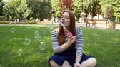 Red-haired girl blows soap bubbles in the park.She smiling and laughing.summer and happiness