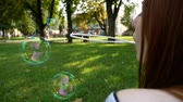 Red-haired girl blows soap bubbles in the park She smiling and laughing summer and happiness Slow Motion