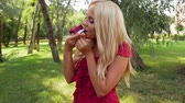 Girl in a red dress eats cake in the park Stock mozgókép
