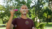 Guy with a beard blows soap bubbles. In the park a sunny day