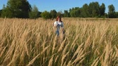 saç modeli : red-haired girl in blue overalls in a field of spikelets Stok Video