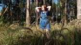divat : Girl in blue overalls walks through the summer forest
