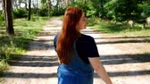 brim : Girl in blue overalls walks through the summer forest