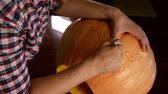 A man carves a Halloween pumpkin. A knife in his hands. Wideo