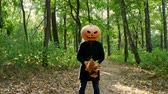 agudo : Cheerful man with a pumpkin on his head scatters the leaves of the forest. Halloween concept.