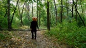Scary pumpkin-headed man chasing after someone in the forest. Knife in hands. Halloween concept.4k