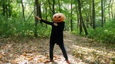Man pumpkin head dancing in the forest, the sun shines brightly