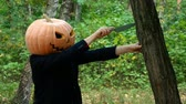 agudo : A man with a pumpkin on his head. He pulls out a knife from a tree. Halloween