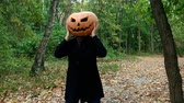 A man with a pumpkin on his head. He grabs his head and waves it