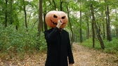 Jack Pumpkinhead in the forest. Finger picking his nose. Guy putting real pumpkin on his head. Halloween concept.