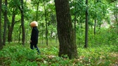 призрак : A man pumpkin head appears from behind a tree with a knife in the forest, Стоковые видеозаписи