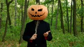 Halloween pumpkin head faces in the autumn forest, play with a knife in the hands