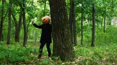 pumpkin head appears from behind a tree with a knife in the forest,