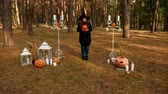 метла : Redhead girl in a witchs hat, in the middle of the forest, surrounded by terrible pumpkins and candles Стоковые видеозаписи