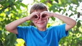 sen : Happy little schoolboy making binoculars with his hands in nature