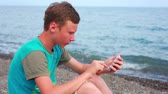 telemóvel : Boy playing on the seashore smartphone