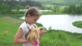 chomik : Child blond girl carrying her guinea pig pet animal. Handheld smooth footage outside. Summertime. Slow motion.