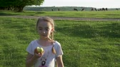 duas pessoas : Adorable girl walking and eating apple. Steadycam shot. Slow motion. Stock Footage