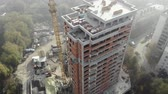 Birds eye view on tower crane in fog standing next to residential building. Flying over the construction site. Drone real time footage. 4K Dostupné videozáznamy