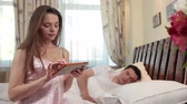 camisola : Beautiful wife watching pics on tablet, husband sleeping in bed