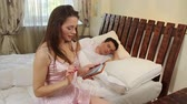 camisola : Cute girl using tablet, tenderly waking up her sleeping partner Vídeos