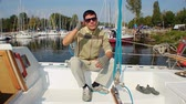 миллионер : Handsome confident male in glasses sitting on luxury yacht