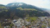 swarovski : Aerial shot of big city, beautiful Alps around it, green downhills, snowy peaks Stock Footage