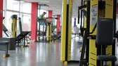 thoroughly : Atmosphere in fitness club, many active people exercising on sports equipment