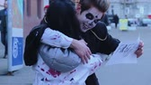 zombi : Young people enjoying Halloween flash mob, having fun with free hugs sign Stock Footage