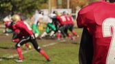 gridiron : Anxious football player watching game, defocused rival teams fighting for ball
