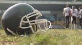 gridiron : Helmet lying on football pitch, team training at gridiron sports school, hobby Stock Footage